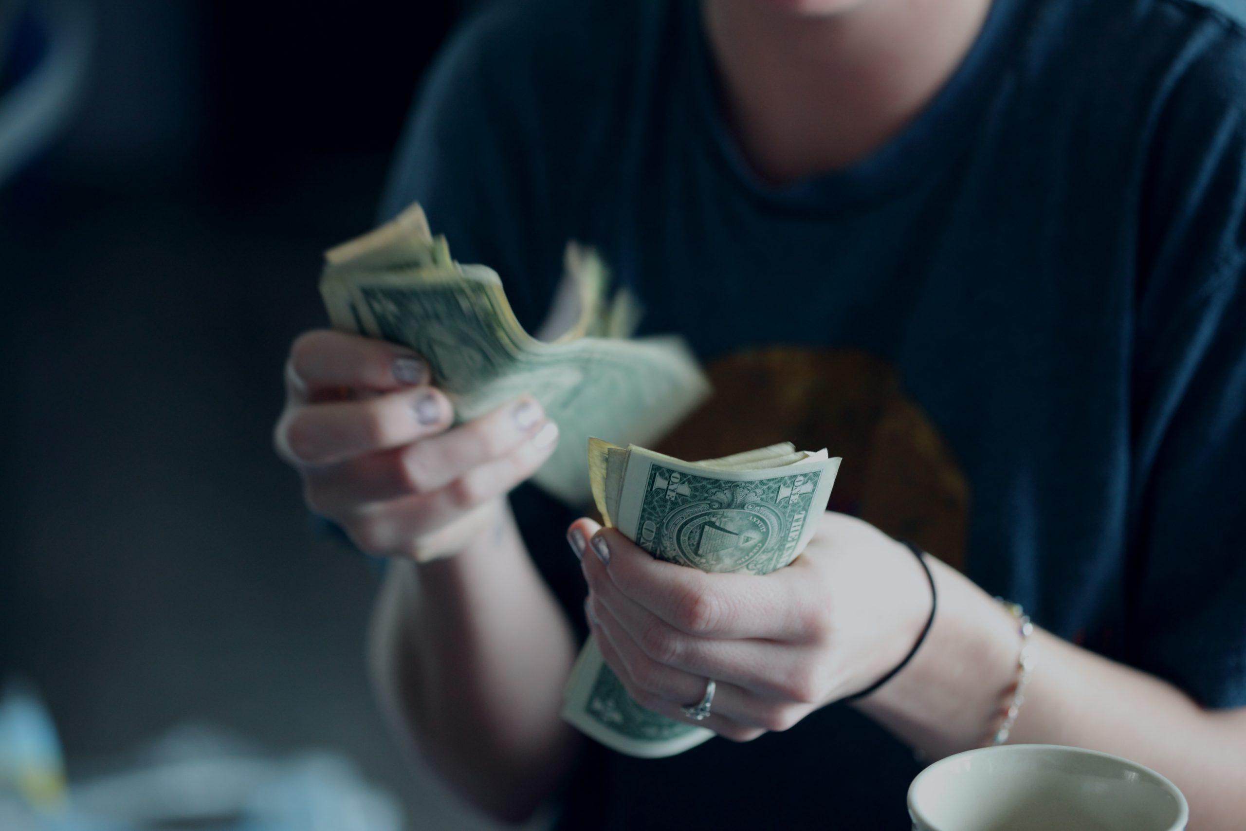 A twenty-four year old woman counting dollar bills.