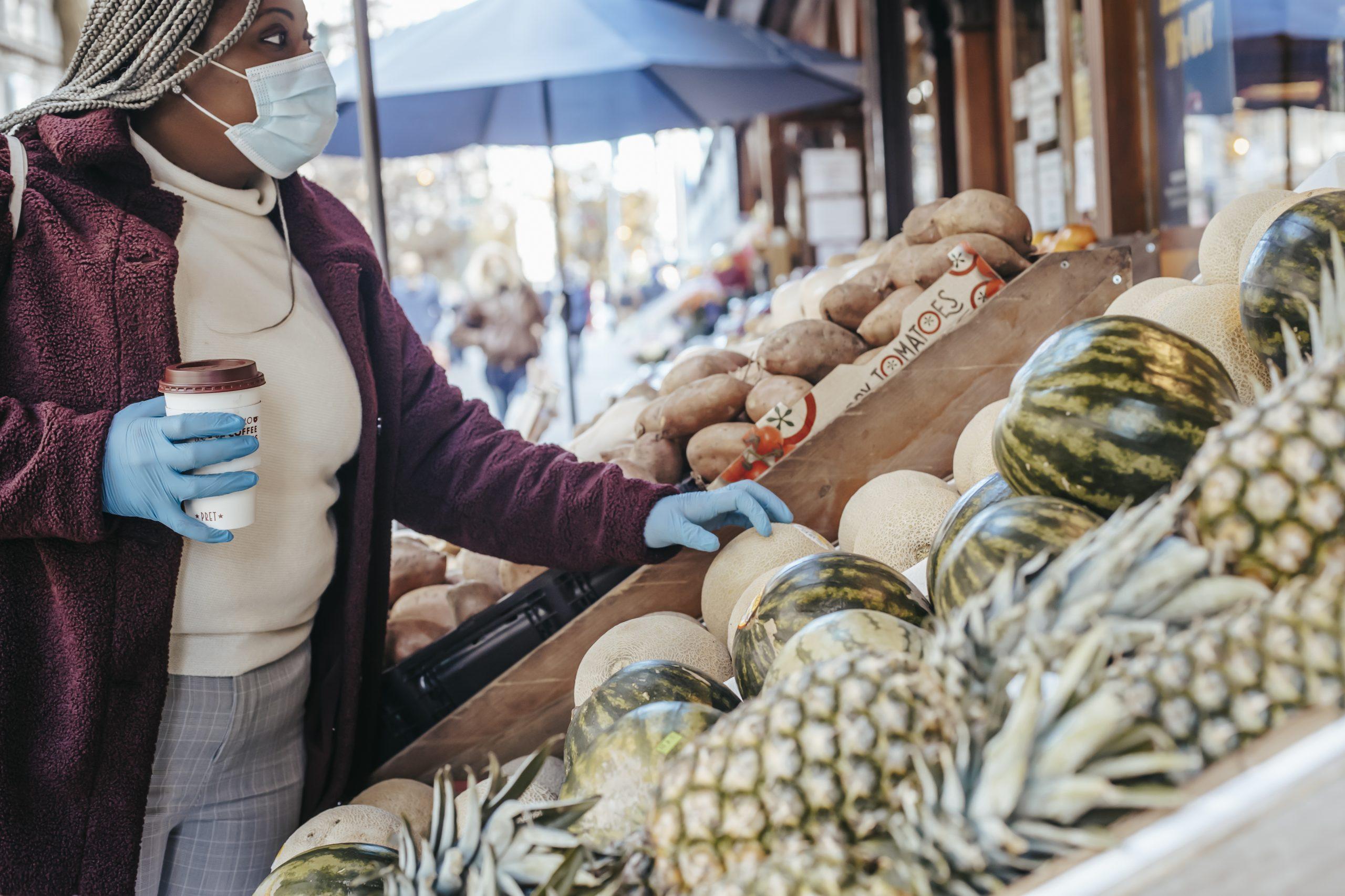 Black woman choosing melon in street market