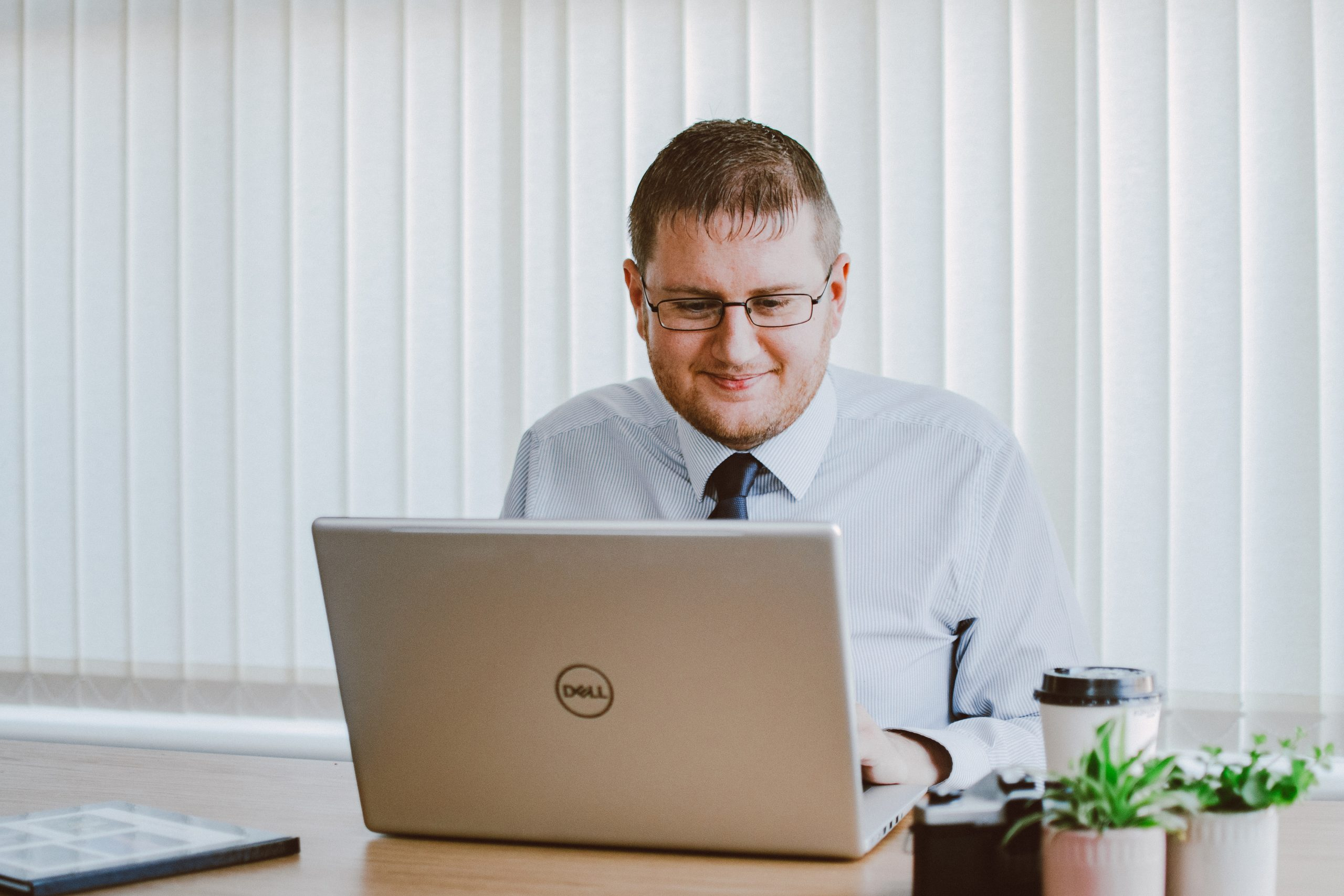 Man in white dress shirt using silver dell laptop