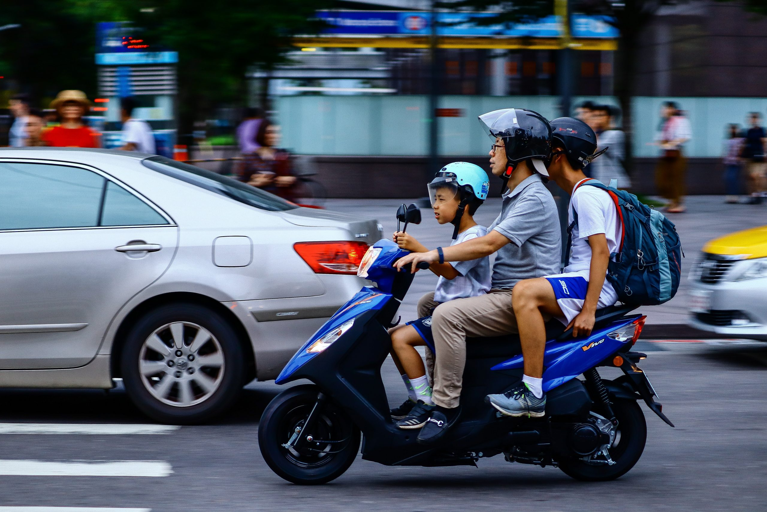 three people riding blue motor scooter